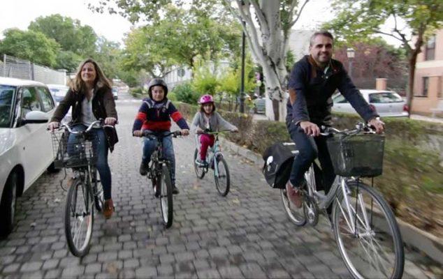Familia feliz paseando en bici
